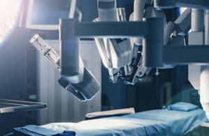 A robotic-assisted surgical device hovers over a hospital bed.