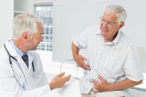 An elderly, male patient points to his stomach pain to a doctor he's consulting with.