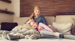 A young mother recovering from breast cancer snuggles with her daughter on the couch.