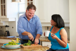 An overweight man chops healthy vegetables while talking with his wife in the kitchen.
