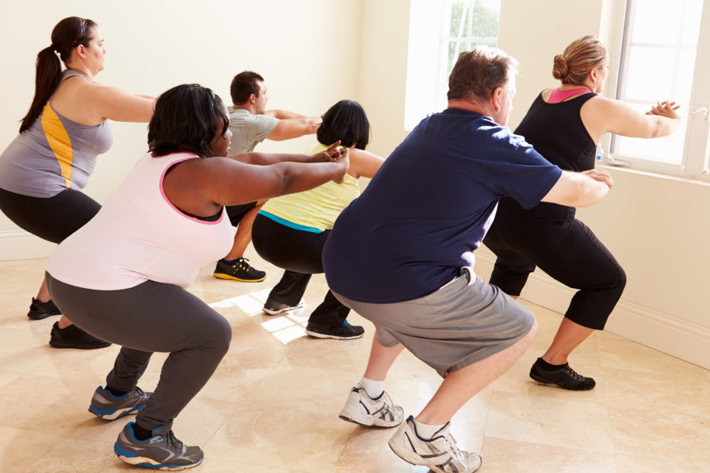 Several middle-aged, plus-size people of varying ethnicities squatting during a group workout class.