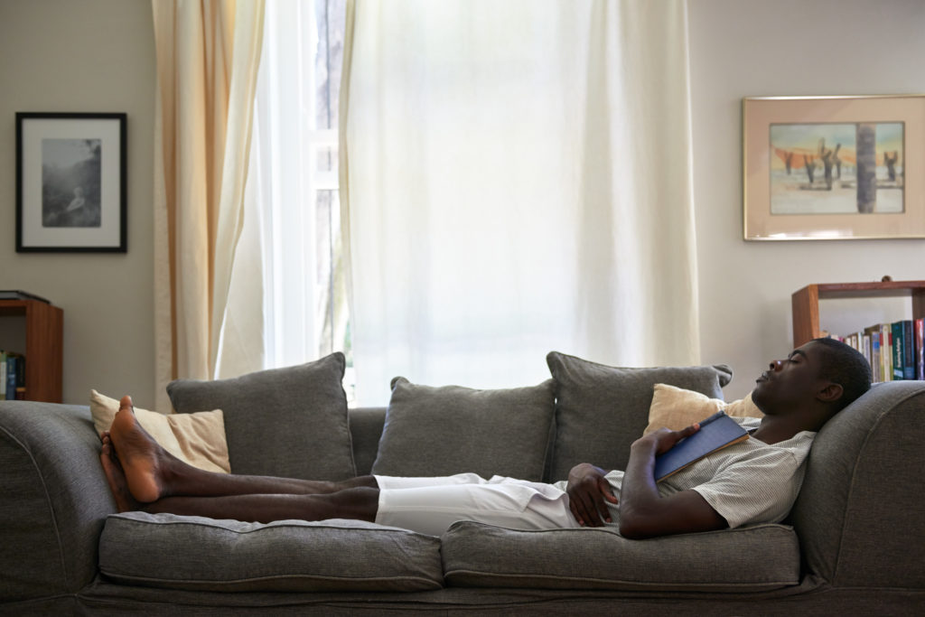 An African American man makes the most of hernia surgery recovery time, resting on a gray couch with a book on his chest.