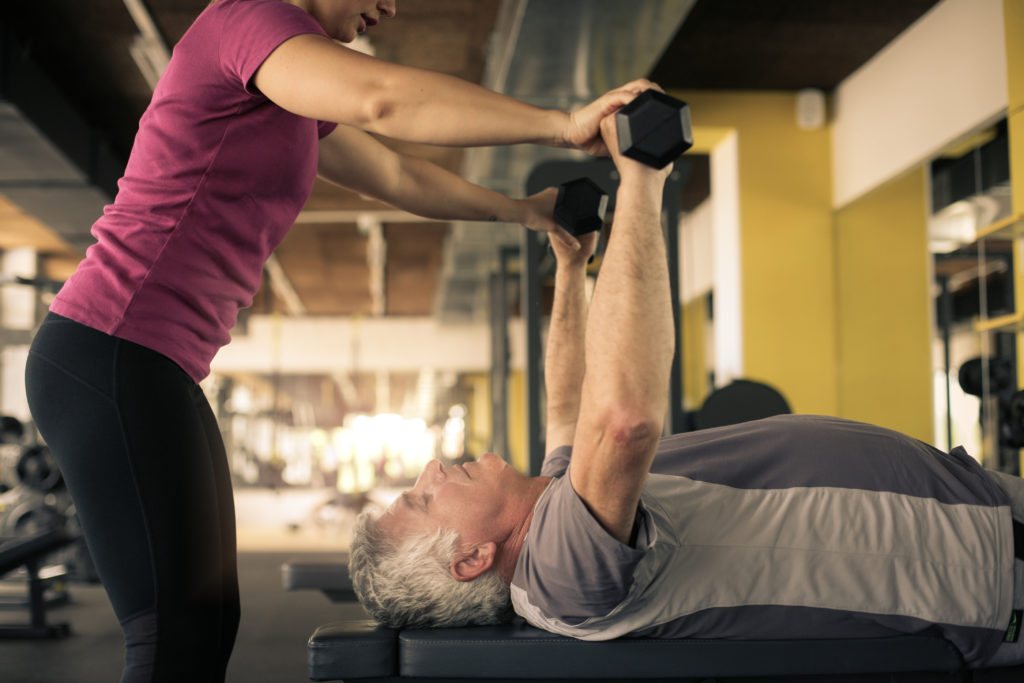 A female athletic trainer wearing a maroon top & pants helps an older gentleman laying prone to perform a shoulder exercise.