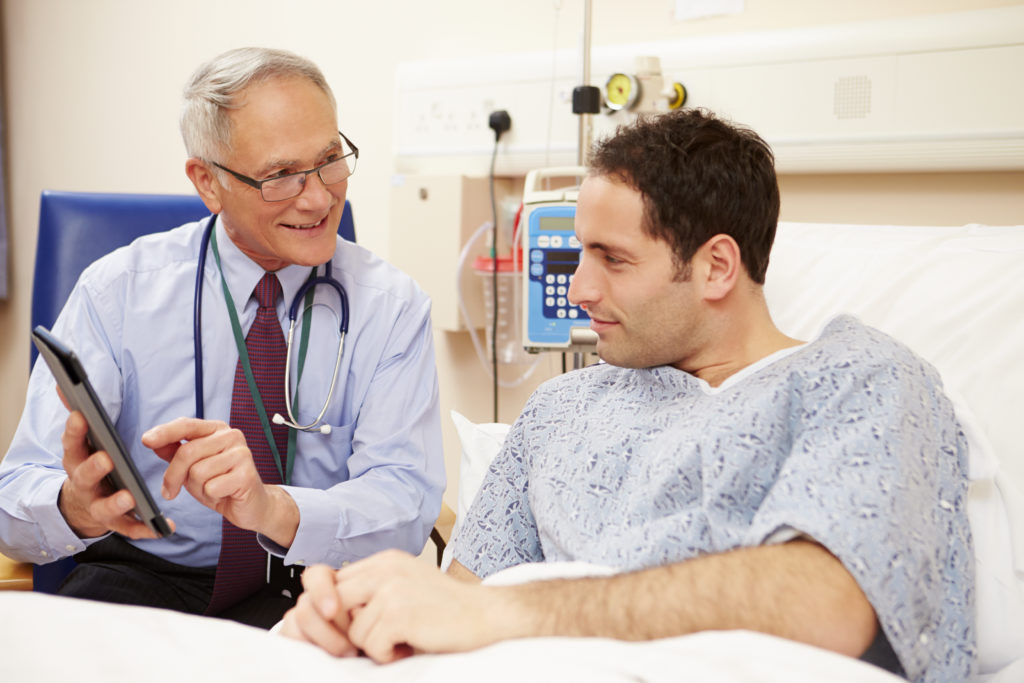 A mature male vascular surgery specialist preps a male patient with brown hair in the hospital prior to surgery.